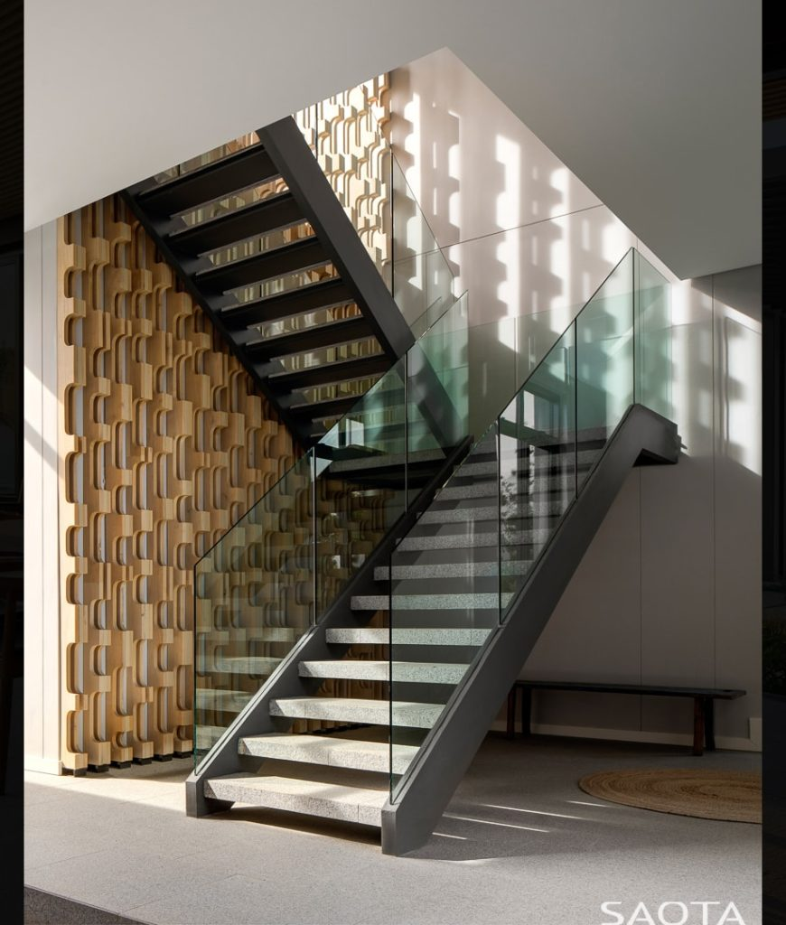 The house's entry features white walls and a staircase. Photo Credit: Adam Letch