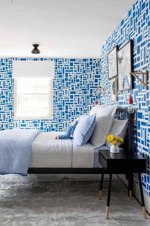 This boy's bedroom boasts stylish blue and white walls paired with the carpet flooring and an elegant black bed frame and side table.