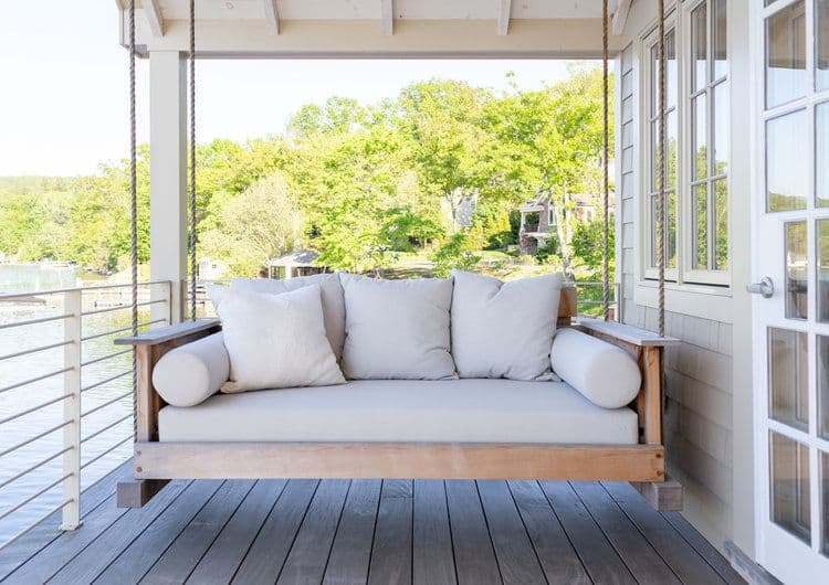 This deck offers a swing with a cushion seats and a set of throw pillows.