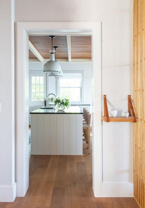 Entryway to the kitchen featuring hardwood floors and white walls. Photo Credit: Raquel Langworthy