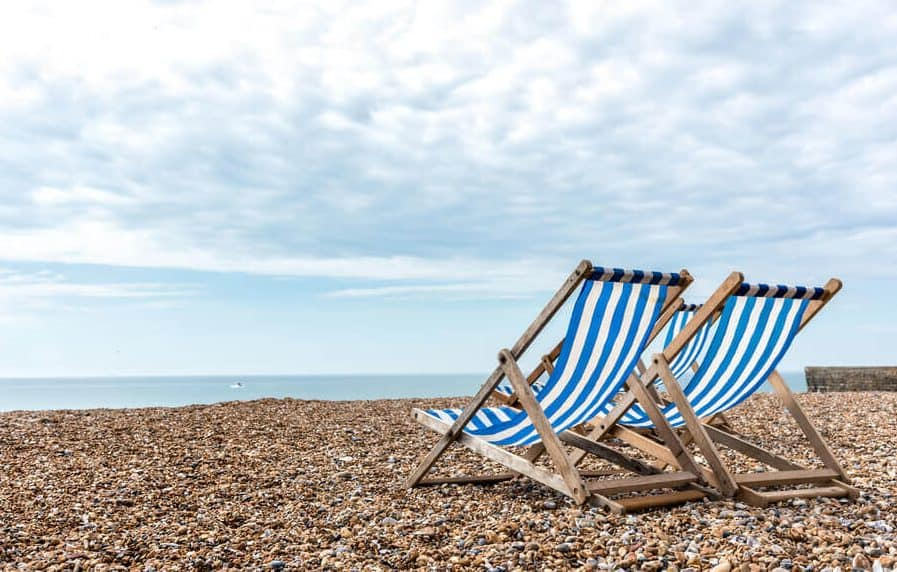 Blue deck chairs on the beach, facing the sea.
