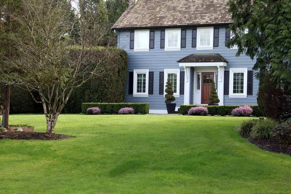 Blue/gray classic home with charcoal gray exterior shutters flanking white trim windows is an absolutely beautiful look on this stunning home. I love it. Rood could use new, darker shingles though.