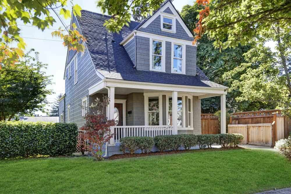 Cozy two story older home with blue exterior with white trim. Visitors are met with a small porch featuring a white railing.