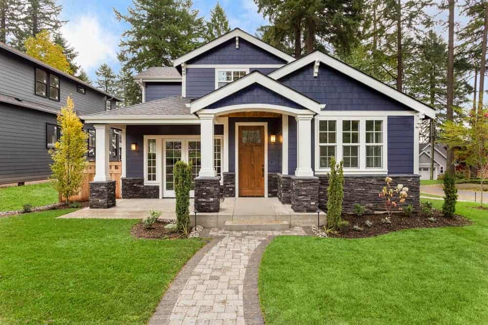 Blue contemporary craftsman style home with shingle siding and white trim.