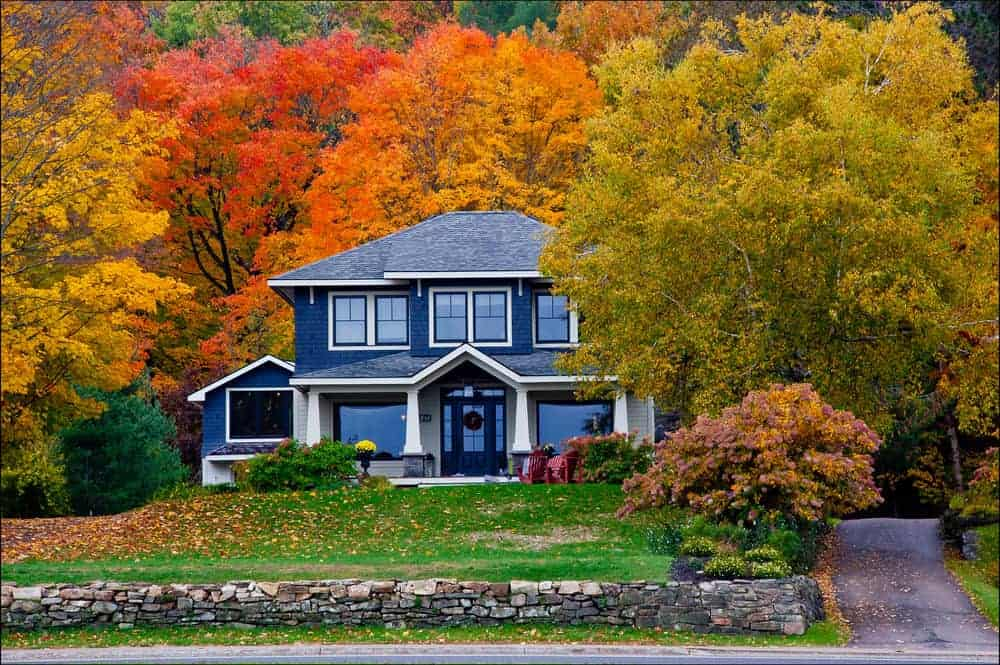 Talk about an incredible scene and property. Large two story home with fairly bright blue exterior set against mountain with Autumn colored leaves all over the property.