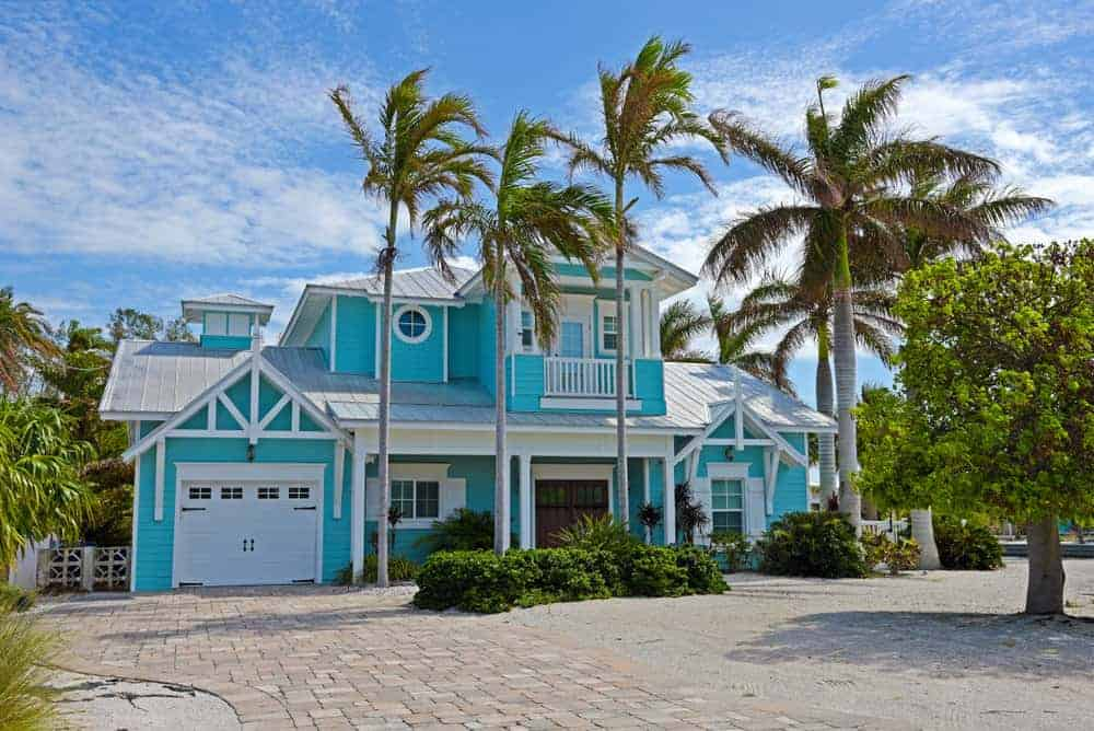 Turquoise Blue Beach Home Surrounded By Palm Trees With Ocean View White Trim And Garage