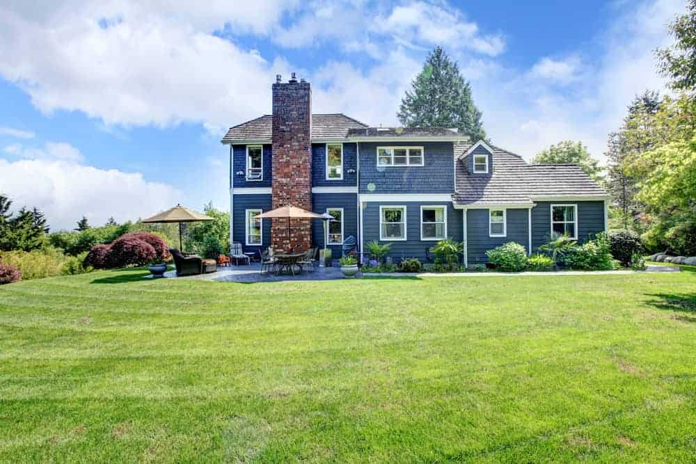 Gorgeous home with outstanding blue for a home's exterior along with white trim. The shingle siding on upper floor works beautifully. I even have admit that the red brick chimney works.