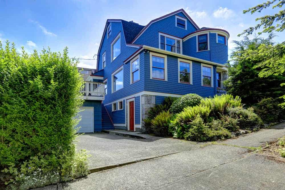 Here's an older home that's been invaded with a bright blue. I do like the very subtle use of some red on the out lines of the trim work. That is a very nice touch along with the red door.