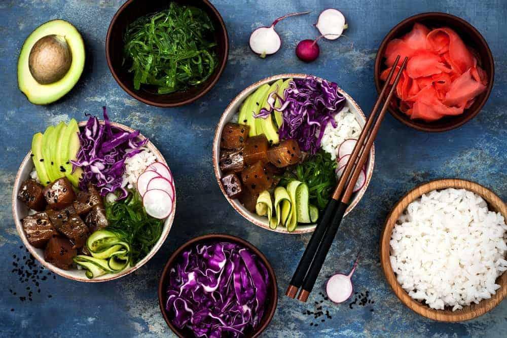 Flat lay of Hawaiian tuna poke bowl with seaweed, avocado, red cabbage, radishes and black sesame seeds.