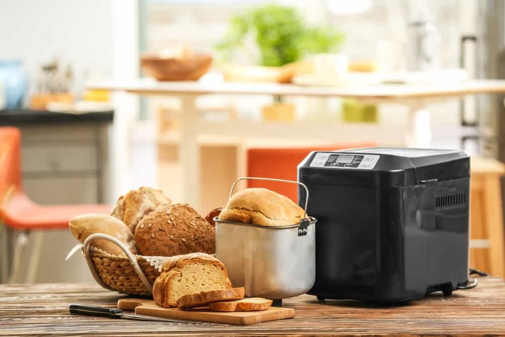 A basket of bread and sliced bread on cutting board beside a bread machine.