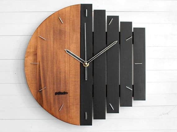 Wooden wall clock in brown and black with a unique shape.