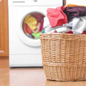 A medium-sized laundry basket iplaced inside the laundry room.