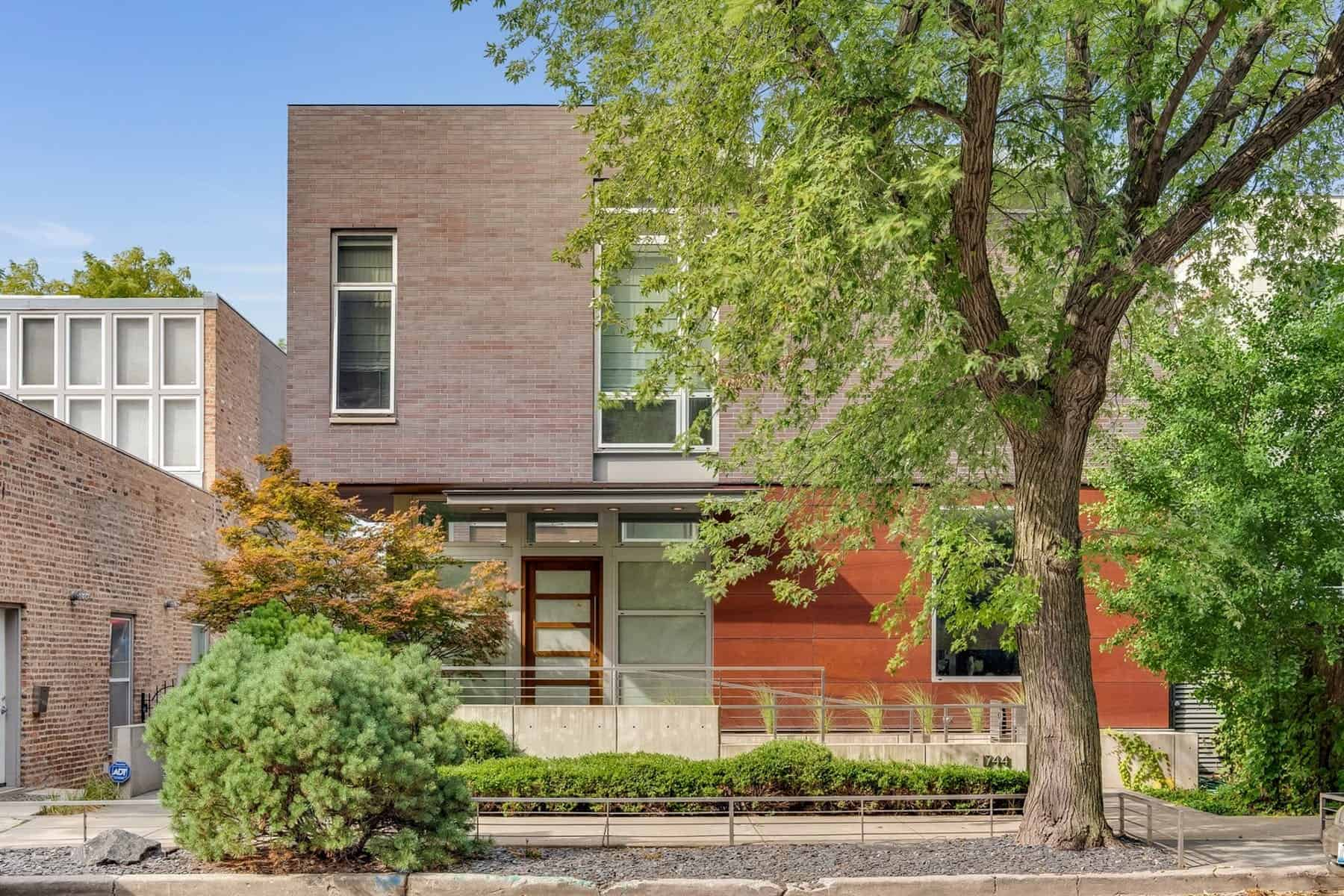 The Cortland residence is made of red brick exterior with healthy plants and trees surrounding the property.