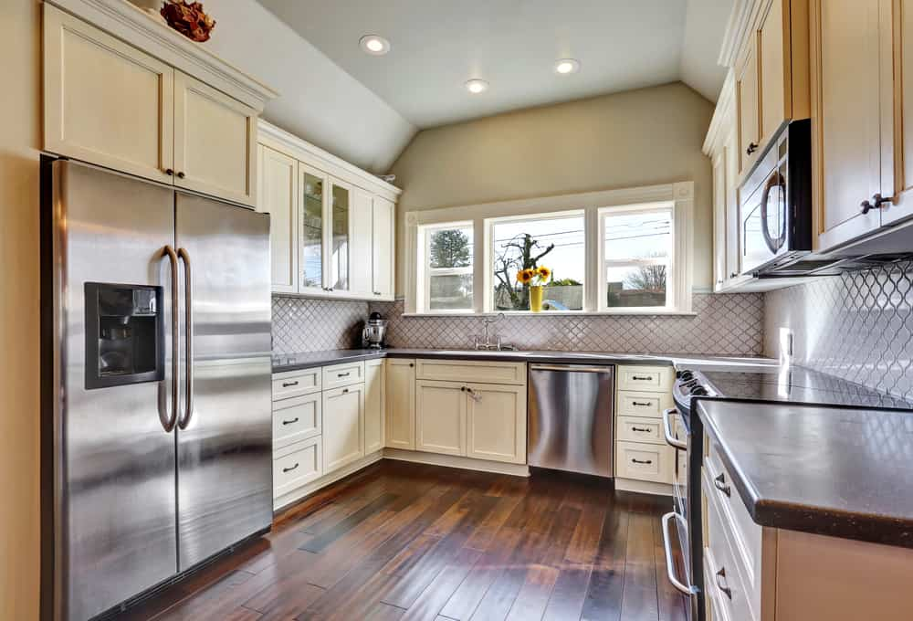 A built-in stainless steel refrigerator in dark hardwood flooring and vaulted ceiling in a kitchen room.