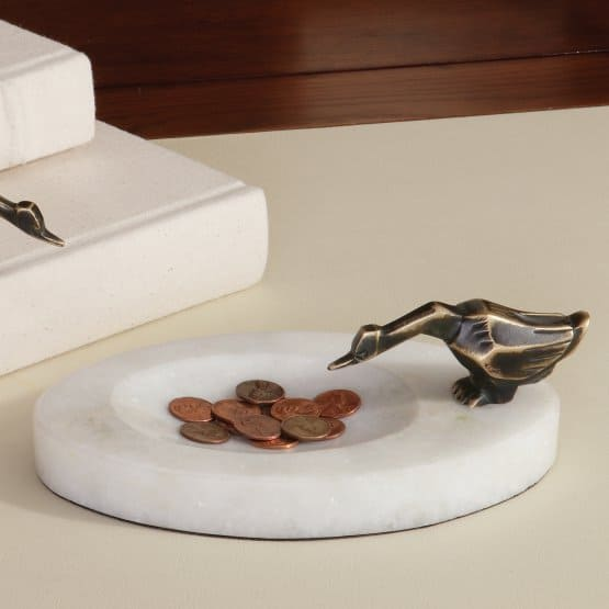 Global Views Deco Duck change bowl with charming desk accent that is crafted from elegant white marble with a brass-toned metal duck perches at the side.