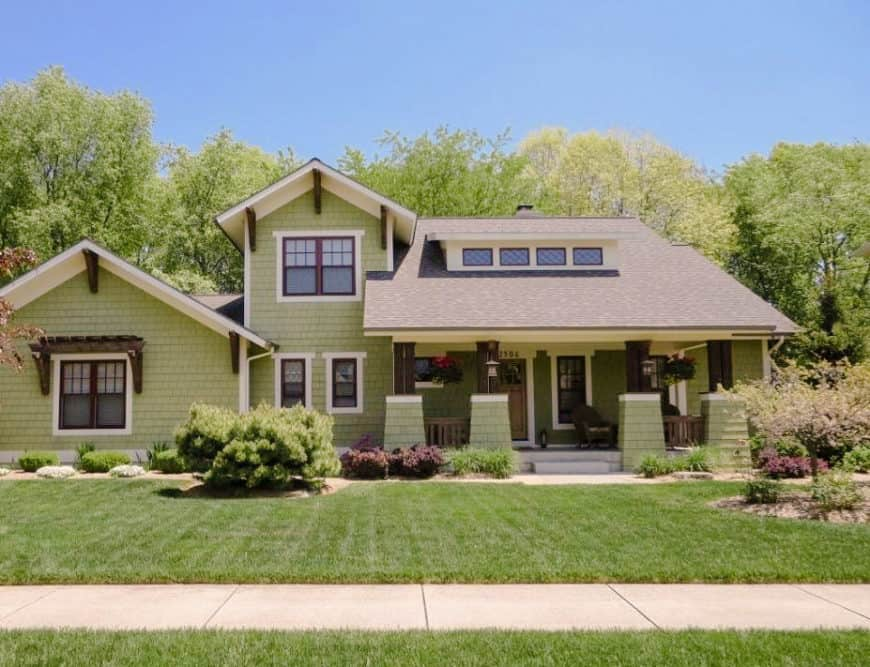 This home boasts green brick tiles exterior. It has a large garden with a well-maintained lawn area, a nice walkway and healthy trees surrounding the property.