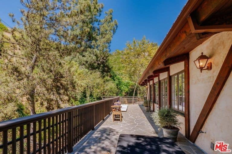 The home has a long balcony overlooking the beautiful landscaping of the property.