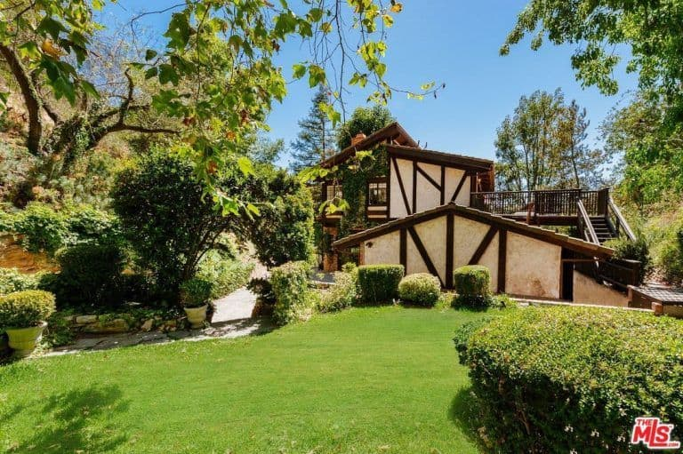 The property also boasts a beautiful garden surrounded by green lawn, plants and trees.