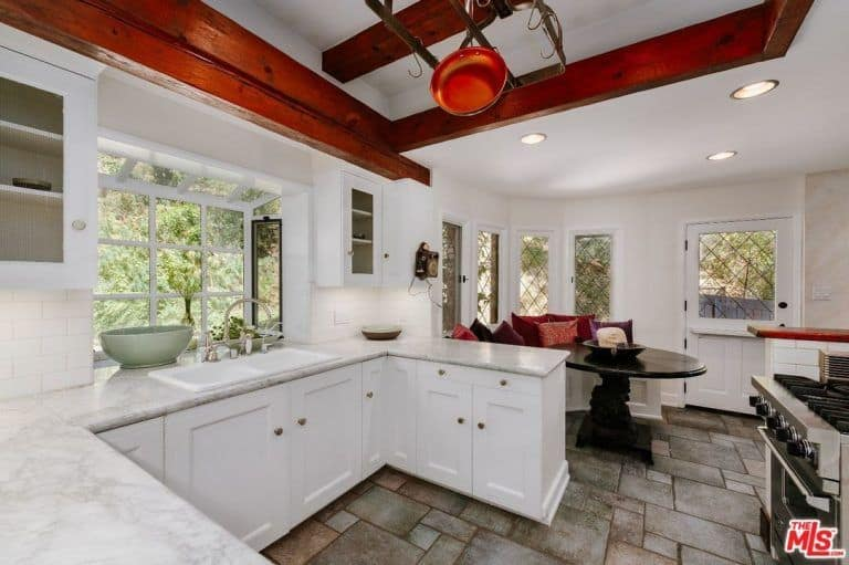 The kitchen features white walls and cabinetry along with top-of-the-line appliances and beams ceiling lighted by recessed ceiling lights.