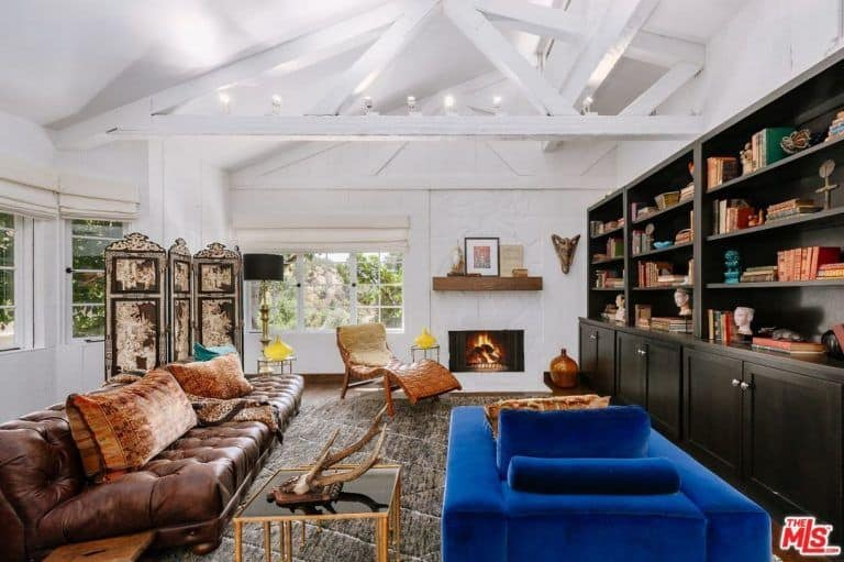White living room boasts blue velvet armchair and leather tufted sofa along with a wicker lounge chair next to the fireplace lined with a wooden mantel.