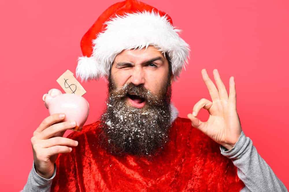 A bearded man in a Christmas spirit holding a small piggy bank.