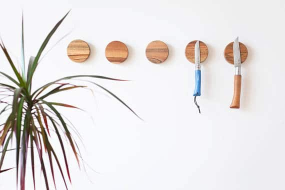 A set of round, wooden knife organizers with a magnetic feature.