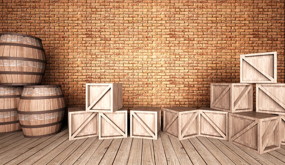 Barrels and crates on wooden flooring and against brick wall.