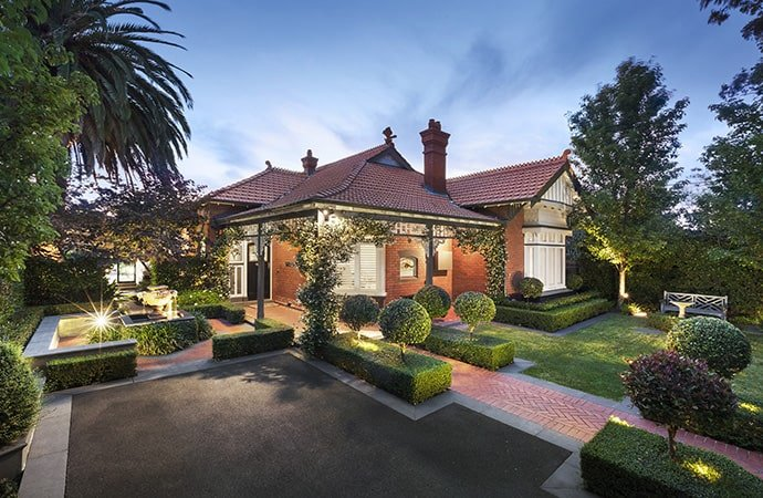 A renovated home boasting a red brick exterior along with a lovely garden area.