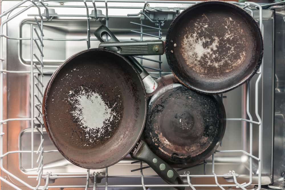 Dirty pans placed inside the dishwasher.