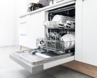 Dishwasher open showing clean dishes and utensils