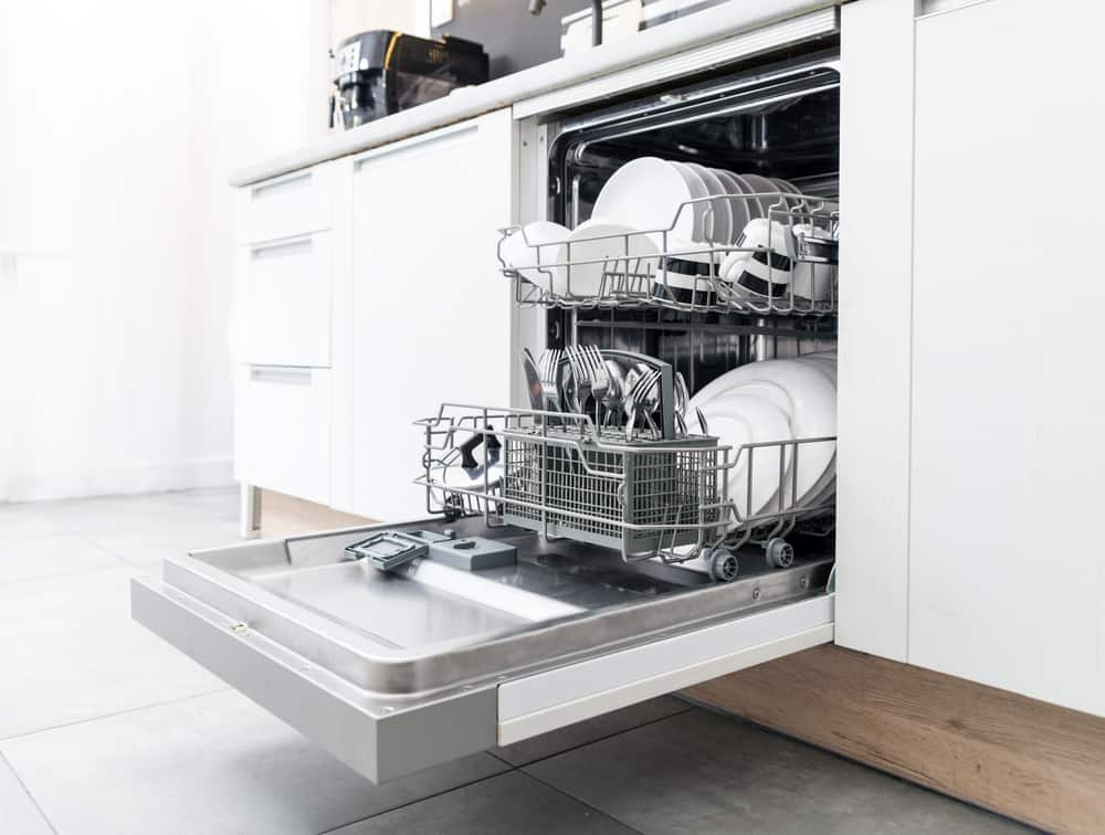 Dishwasher with clean dishes in a white kitchen.