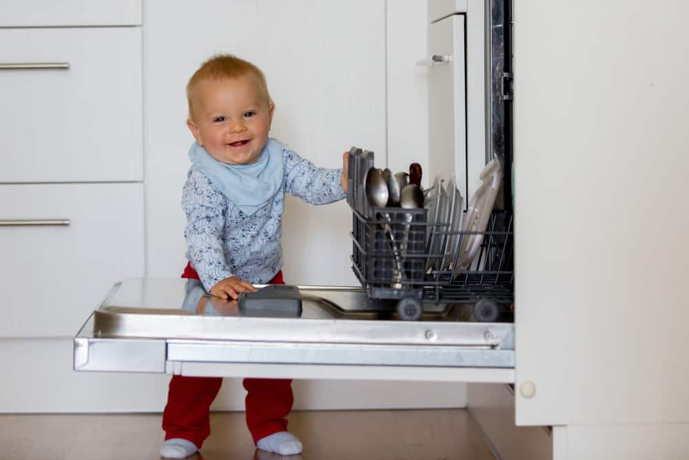 A toddler stands smiling by an open dishwasher.