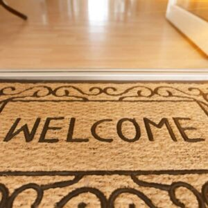 """A doormat in a medium Tan shade with a """"Welcome"""" text design."""