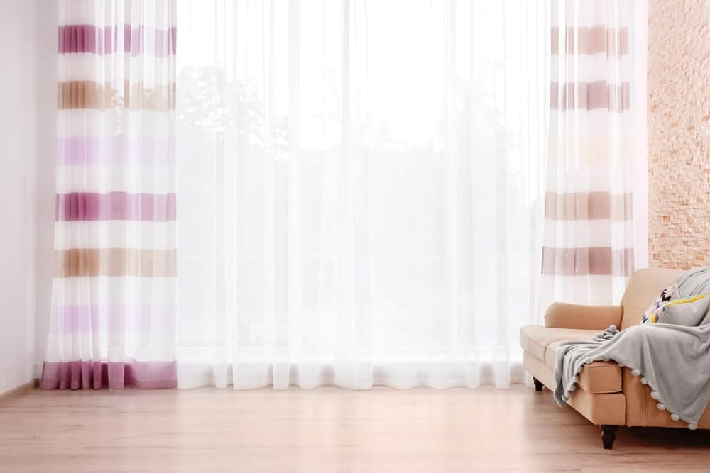 Light-colored drapes cover a full window in the living room.