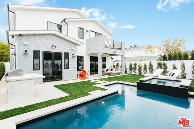 The home's backyard features a beautiful lawn and a pool along with sitting lounge.