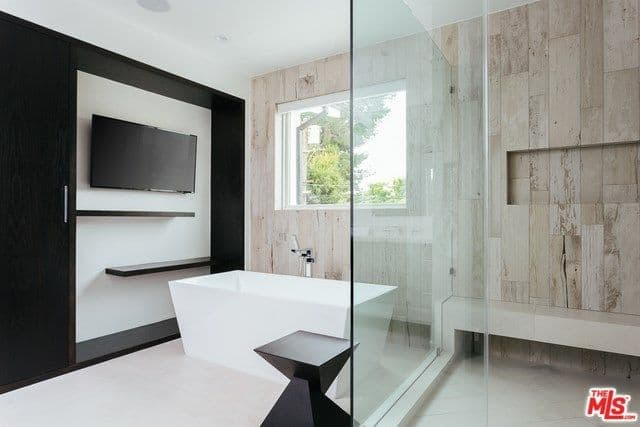 A modish primary bathroom offering a wide screen TV on the wall while soaking in the freestanding tub. There's an open shower too.