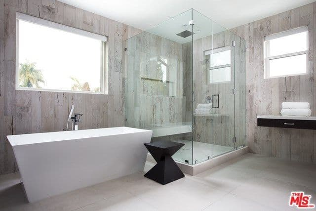 This modish master bathroom offers a stunning freestanding tub and a corner shower area. The walls look so stylish.