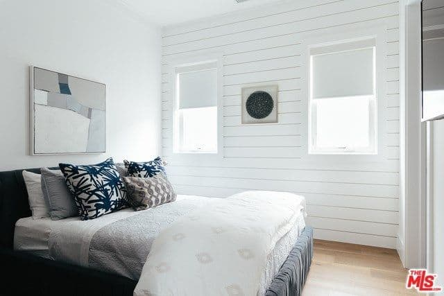 Another bedroom covered by white walls features a comfy bed and some wall decors along with a hardwood flooring.