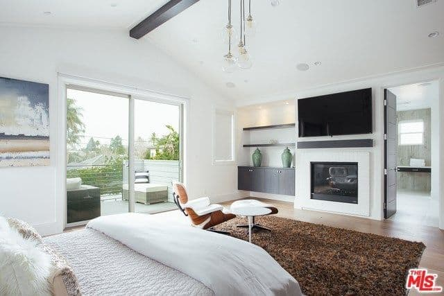 The master bedroom features comfortable large bed and a nice sitting place on top of the stylish rug in front of the TV on top of the fireplace. There's a doorway leading to the balcony featuring glass doors.