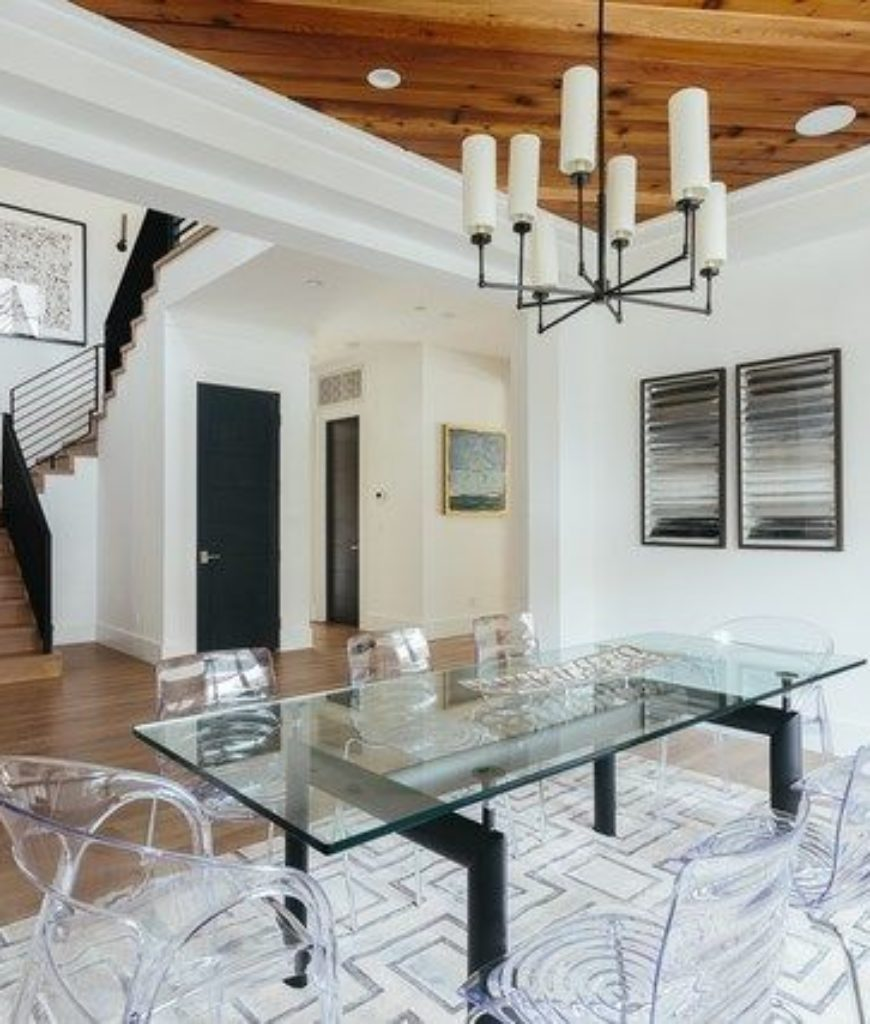 The dining room boasts glass dining table and glass chairs along with candle chandelier and a stylish rug to complete the modish dining set.