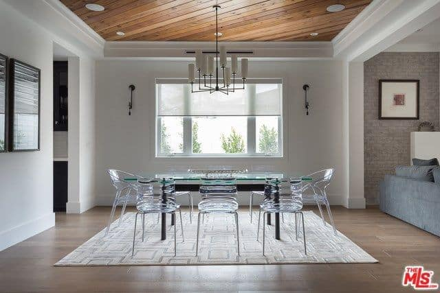 Stylish dining room with a glass dining set on a patterned rug illuminated by wall sconces and a white chandelier that hung from the wood plank tray ceiling.