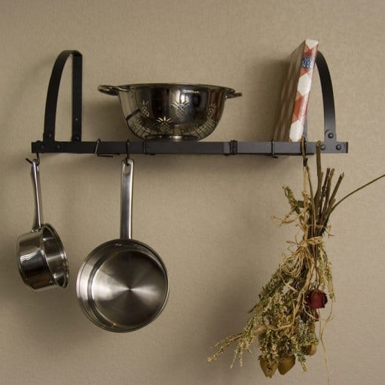 Expandable wall-mounted shelf pot rack on beige wall background.