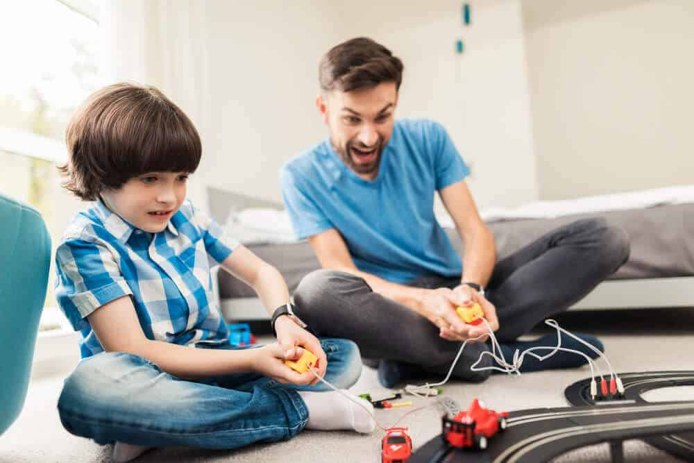 Father and son playing with toy cars.