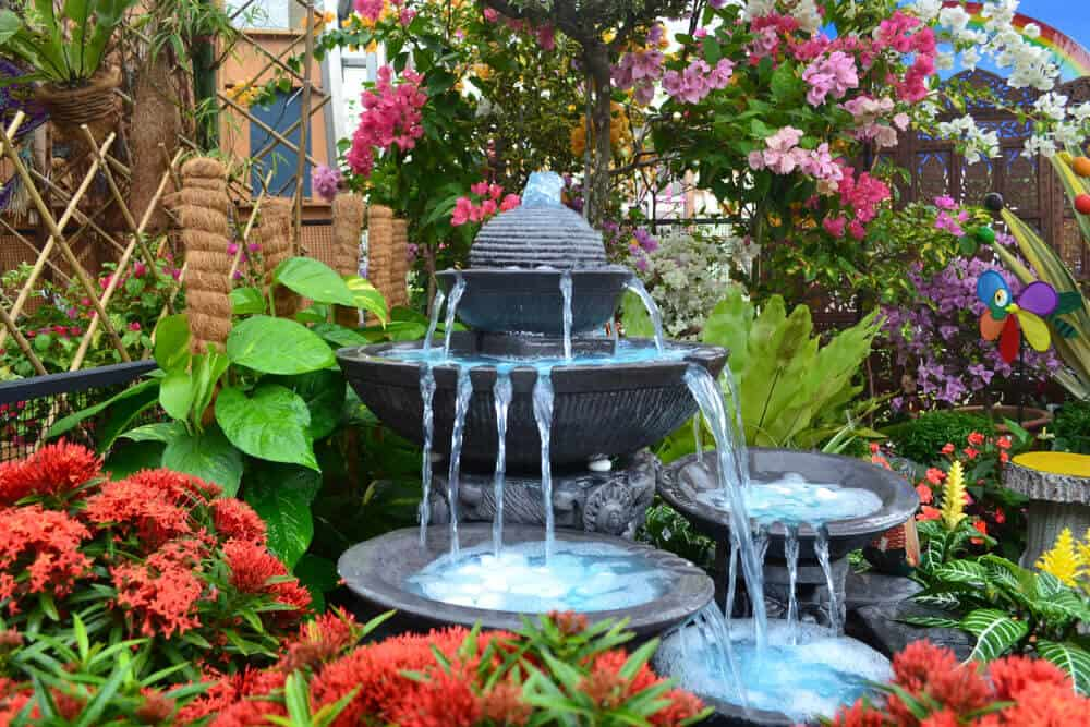 A stone, cascading fountain with multiple tiers placed in a garden full of plants and flowers.