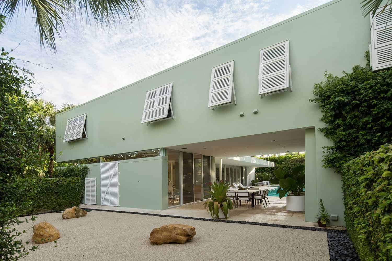 Large modern home with a green exterior. It features great outdoor amenities such as outdoor dining, a swimming pool and sitting lounges.