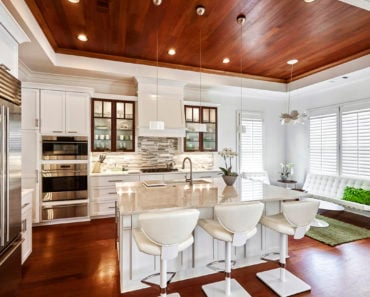 Kitchen with incredible wood ceiling and recessed light creating a more natural appearance in an otherwise all white kitchen design.