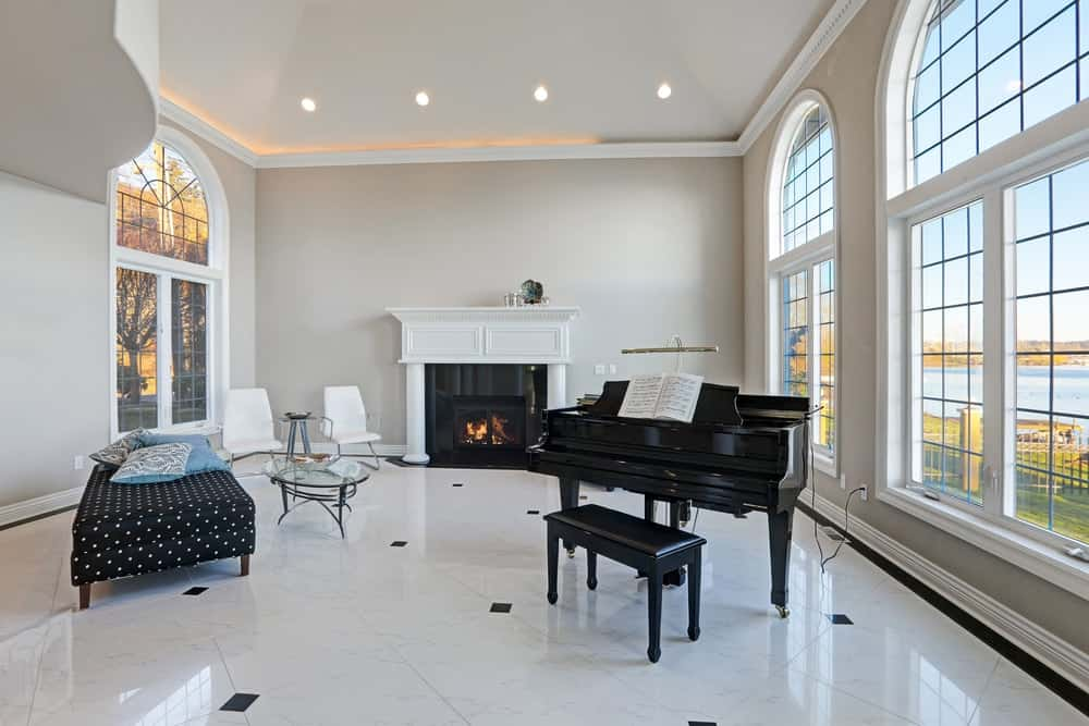 A black grand piano stands near the arched window in this high-ceilinged luxury living room with ivory walls, traditional fireplace, cozy sitting area and marble tile flooring.