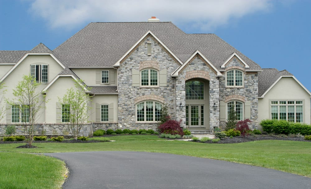 Green McMansion with green exterior shutters. The exterior is a combination of green stucco and grey stone.