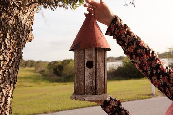 Handcrafted birdhouse with a cylindrical body and a cone-shaped roof.
