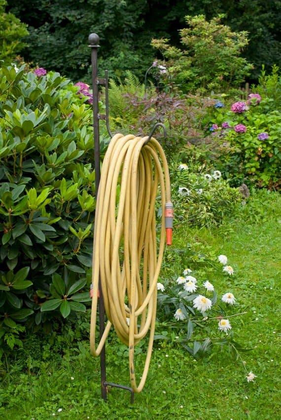 A handmade, free-standing metal hose holder for gardens.